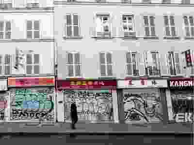 A man walks past closed shops in Paris on March 15, 2020, a day after France ordered the closure of all non-essential public places including restaurants and cafes, amid the COVID-19 outbreak, caused by the novel coronavirus. - France will progressively reduce long-distance train, bus and plane travel over the coming days in a bid to limit the spread of the coronavirus, the government announced on March 15. The country has already shuttered cafes, restaurants, schools and universities and urged people to limit their movements.