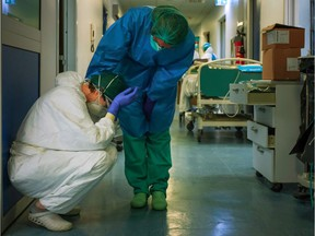 A nurse wearing protective mask and gear comforts another as they change shifts on March 13, 2020 at the Cremona hospital, southeast of Milan, Lombardy, during the country's lockdown aimed at stopping the spread of the COVID-19 (new coronavirus) pandemic.