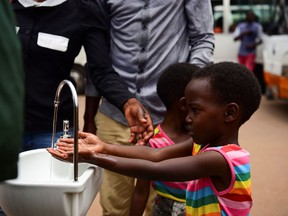 Twin sisters, Emeline and Eveline, wash their hands at a public hand washing station as a cautionary measure against the coronavirus at Nyabugogo Bus Park in Kigali, Rwanda. March 11, 2020. REUTERS/Maggie Andresen