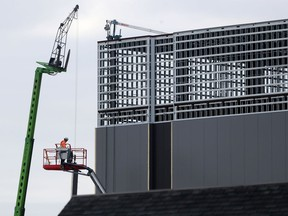 Construction workers working on a building on Industrial Ave. in Ottawa Tuesday March 24, 2020.