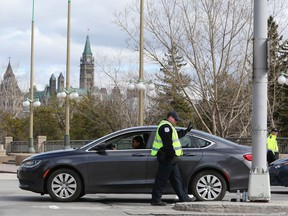 Gatineau Police officers spot-check traffic leaving from and arriving into Gatineau on the Portage Bridge on Wednesday. More than a river separates West Quebec from Ottawa now.