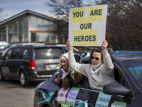 A parade of cars bearing positive messages drives in front of a long-term care centre in the Toronto area.