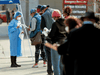 People wait in line to b0e tested for COVID-19 outside Roseland Community Hospital in Chicago, Illinois, April 7, 2020.