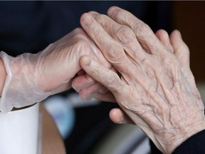 An employee holds the hand of a person at the elderly residence Christalain following the coronavirus disease (COVID-19) outbreak in Brussels, Belgium April 14, 2020. REUTERS/Yves Herman ORG XMIT: GDN