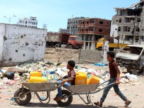 Children return home after filling their jerrycans with water   amid a severe shortage in the southern Yemeni city of Aden, on April 29. The war-ravaged country is now also battling novel coronavirus.