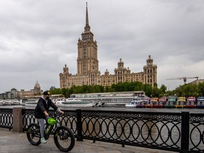 A woman wears a protective face mask as she rides a bike along the Moskva river embankment in central Moscow on May 10, 2020.