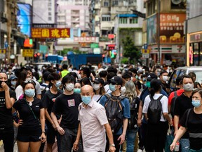 Protesters look towards a group of riot police in the Mongkok district of Hong Kong on May 27, 2020, as the city's legislature debates over a law that bans insulting China's national anthem.