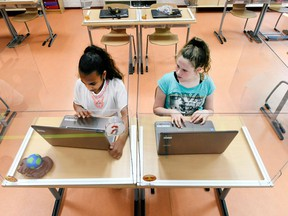 FILE PHOTO: Pupils sitting behind partition boards made of plexiglass attend a class at a primary school, during the COVID-19 outbreak, in Den Bosch, Netherlands, May 8, 2020.