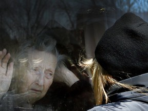 Diane Colangelo visits her 86-year-old mother Patricia through a window at the Orchard Villa long-term care home in Pickering on Wednesday April 22, 2020. Both daughter and mother were in tears.