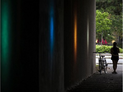 A cyclist stands in the underpass out of the rain on the National Capital Commission recreational trail near Mill Street Brewery on Saturday afternoon.
