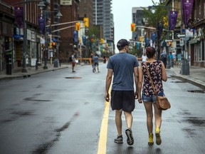 A couple strolls down Bank Street, closed to traffic during the pandemic. Everyone fears COVID-19, but some people have less to fear than others.
