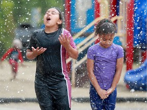 While Sofiya Ammar, 9 (right), seemed to just brave the chilly waters, her older sister, Mariam, 11,  drank in the cold water at the Barrhaven splash pad Monday — a welcome relief from the oppressive heat and humidity in the capital recently.