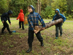 Teddy (L) and Brennan (R), grade 4 students at Rivière Rideau school in Kemptville, help build an outdoor structure during forest school period, October 07, 2020.