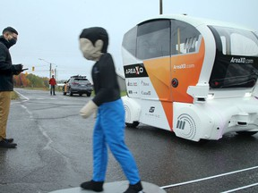 Area X.O technical project manager Tanissan Thavathurai moves a life-size figure across a road to test the auto-braking of an autonomous shuttle.