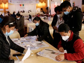 Members of the Departmental Electoral Tribunal count votes after a nationwide election in La Paz, Bolivia, Oct. 21.