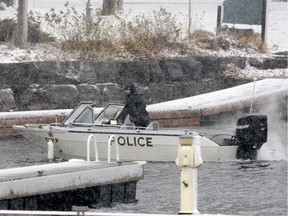 An Ontario Provincial Police officer prepares to bring a police boat back to shore Sunday afternoon in Brockville after police recovered the remains of a missing diver from the St. Lawrence River.