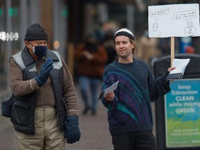 A man hands out anti-mask pamphlets in Edmonton on Oct. 30.