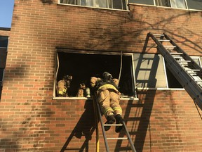 Ottawa firefighters at work evacuating family from smokey fire in city's south end.