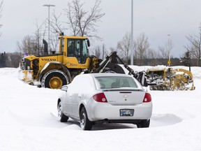 A file photo of a CIty of Ottawa city plough clears the parking lot of snow at the Fallowfield Transit Station following a winter storm in Ottawa on February 13, 2019.