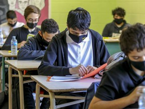 Masked high-students read at their desks in this Montreal high school.