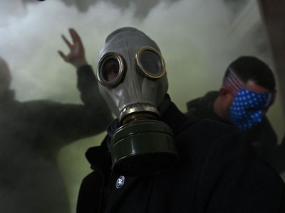 """TOPSHOT - A supporter of US President Donald Trump wears a gas mask as he protests after storming the US Capitol on January 6, 2021, in Washington, DC. - Demonstrators breeched security and entered the Capitol as Congress debated the a 2020 presidential election Electoral Vote Certification. President-elect Joe Biden denounced the storming of the US Capitol as an """"insurrection"""" and demanded President Donald Trump go on television to call an end to the violent """"siege."""" (Photo by Brendan SMIALOWSKI / AFP)"""