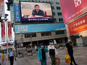 Big Brother is watching: People wearing face masks walk under a giant screen showing news footage of Chinese President Xi Jinping in Beijing.