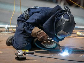 FILE: A construction worker welds metal on a ship.
