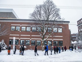 Eligible vaccine recipients, mostly front-line workers, lined up outside The Ottawa Hospital Civic Campus, Saturday Feb. 27, 2021, in the snowstorm that hit the capital, to receive their much anticipated COVID-19 vaccine.