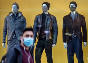 A pedestrian wearing a mask walks through Yorkville with mannequins wearing masks in a clothing store window during the Covid 19 Pandemic, Monday October 5, 2020.