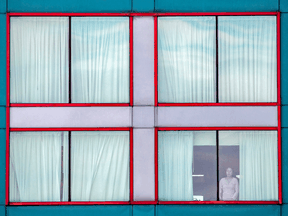 Files: A person looks out of a window at a quarantine hotel.