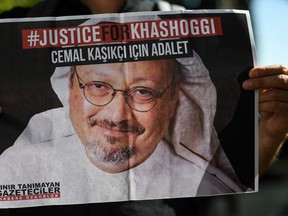 In this file photo taken on Oct. 2, 2020, friends of murdered Saudi journalist Jamal Khashoggi hold posters bearing his picture as they attend an event marking the second-year anniversary of his assassination.
