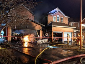 Ottawa Fire Services crews fight a garage fire that spread to a neighbouring residence on Burntwood Avenue, near Nottingham Court, in Barrhaven on the evening of Thursday, March 25, 2021.