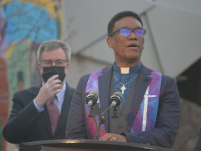 Rev. Anthony Bailey of Parkdale United Church speaks at Thursday's memorial interfaith service commemorating the anniversary of the first COVID-19 death in Ottawa while Mayor Jim Watson looks on.