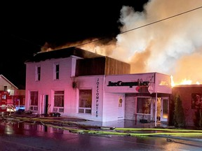 Firefighters battle a blaze that left nine people homeless and destroyed two businesses in Spencerville early Friday.