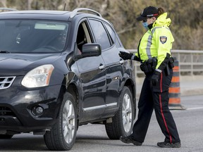 An Ottawa Police Services officer screen a traveller crossing the Chaudière Bridge on Tuesday.