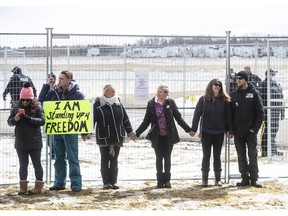 Supporters gather outside GraceLife Church near Edmonton, Alta., on Sunday, April 11, 2021 to protest not being able to attend in-church services. The church was fenced off by police and Alberta Health Services in violation of COVID-19 rules.