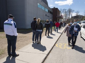 """People line up at a COVID-19 vaccination centre in Deux-Montagnes on Friday. """"It's a race against time. We have to vaccinate the most people possible so they can't transmit the disease,"""" said Michel Roger, medical director of Quebec's public health laboratory."""