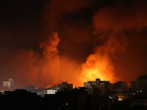 Smoke billows from a fire following Israeli airstrikes on multiple targets in Gaza City, controlled by the Palestinian Hamas movement, early on May 16, 2021. - Israel pummelled the Gaza Strip with air strikes, killing 10 members of an extended family and demolishing a building housing international media outlets, as Palestinian militants fired back barrages of rockets.