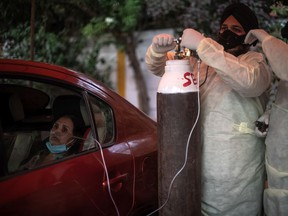 NEW DELHI, INDIA - MAY 03: Volunteers treat patients suffering from Covid-19 with free oxygen at a makeshift clinic in a parking lot outside the Gurdwara Damdama Sahib on May 03, 2021 in New Delhi, India.
