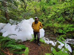 Townhouse resident Tom Ulanowski stands beside the foam floating on Clayburn Creek.