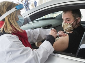 Alex Smirnov gets a COVID-19 vaccination from Annie Halinka Sanson at a demonstration of a drive-through vaccination site, Tuesday, May 4, 2021 in Montreal. The site will be able to give 4,000 doses a day.THE CANADIAN PRESS/Ryan Remiorz ORG XMIT: RYR103-05-04