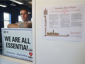 Zachary Boissinot poses with a sign at his A Foot Above Fitness gym in Ottawa Wednesday. Boissinot says he will fight the $4000-plus fines he has received and contends that gyms should be essential businesses because they help keep people healthy during a health crisis.