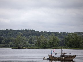 An unidentified man adjusts a Canadian flag flying on his boat while on the Ottawa River by Petrie Island Beach on Saturday.