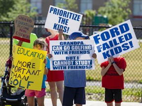 Children and parents protest against school closures near Sir Winston Churchill Public School in Ottawa on Wednesday.
