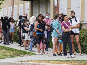 Shoppers lined up around the building to shop at a Value Village store on Hazeldean Road on the first day of Stage 1 of the provincial reopening on Friday, Jun. 11, 2021.