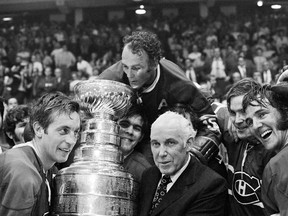Montreal Canadiens' Henri Richard, centre, who scored the game-winning goal, peers into the Stanley Cup held by team captain Jean Béliveau, left, and NHL Commissioner Clarence Campbell in Chicago, on May 18, 1971.