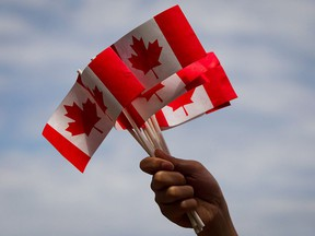 A volunteer hands out flags in a file photo from Canada Day festivities in Vancouver on July 1, 2013.
