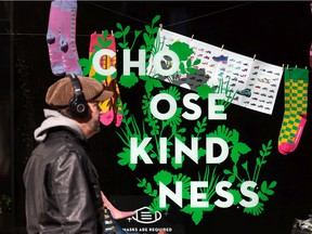 """People in COVID-19 masks pass a positve sign reading """"Choose Kindness"""" in Edmonton."""