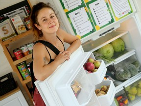 Parkdale Food Centre employee Alexia Smith shows what's inside the new community fridge and pantry outside the centre.