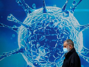 A man wearing a protective face mask walks past an illustration of a virus outside a regional science centre amid the coronavirus disease (COVID-19) outbreak, in Oldham, Britain on August 3.